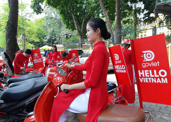 "A woman, wearing the traditional Vietnamese long dress ""ao dai"", promotes Go Viet, the Vietnamese version of the Indonesian Gojek company, during its launch ceremony in Hanoi"