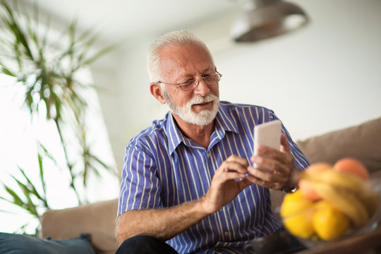 Handsome old man using a smartphone and smiling while sitting on couch at home