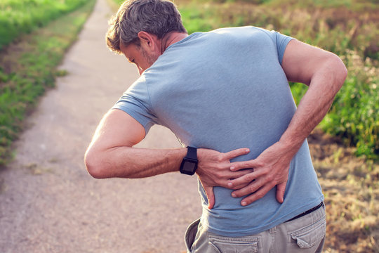 People, healthcare and problem concept - unhappy man suffering from pain in back or reins outdoor