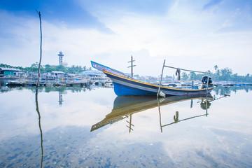 Reflection of Kolae boat, traditional Thai-Malayu fishing boat on the river at sunset. The Bang Nara River, Narathiwat, Thailand.