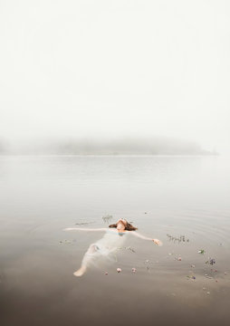 Young woman floating on water in mist