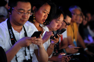 Attendees use their smartphones during a Dyson product launch event in Beijing