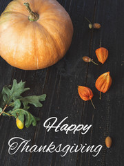 Happy thanksgiving with pumpkin, acorns and greeting inscription on dark background