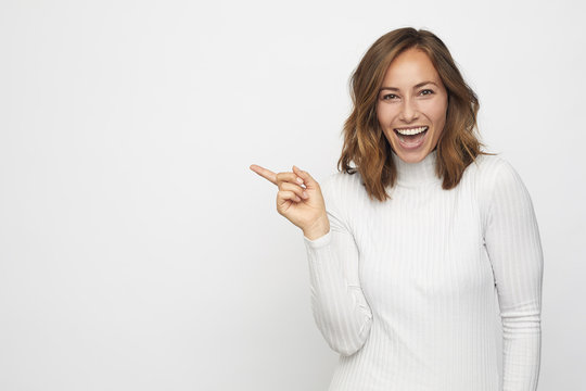 young woman pointing at copyspace looks in camera