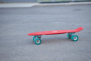 Red penny board is on the road, close-up. Skateboard and space for text.