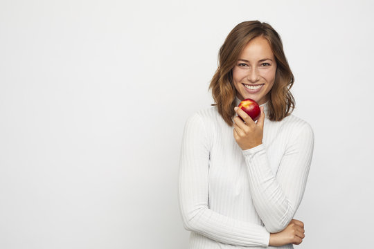 young woman with red peach looks in camera