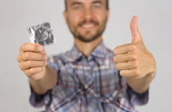 man in plaid shirt holds a new condom in hand, make gesture thumb up, joy and anticipation of pleasure