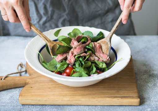 Bowl with spinach salad, onion, cherry tomatoes, steak slices and spices. Woman stirs salad with wooden spoons