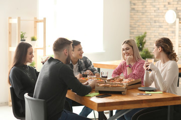 Young people eating pizza at table indoors