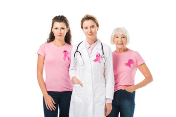 doctor and women with breast cancer awareness ribbons looking at camera isolated on white