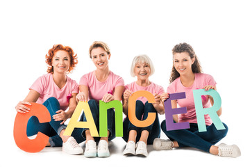 women in pink t-shirts holding colorful letters with word cancer and smiling at camera isolated on white