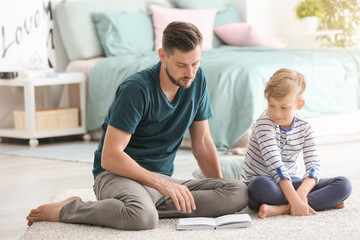 Father and his son reading book together at home