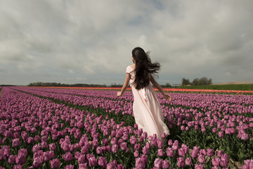 Girl standing in tulip field
