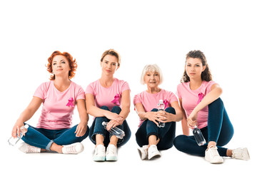 women in pink t-shirts with breast cancer awareness ribbons holding bottles of water and looking at camera while sitting isolated on white