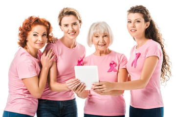 women in pink t-shirts with breast cancer awareness ribbons holding digital tablet and smiling at camera isolated on white