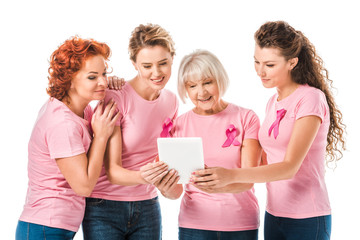 smiling women in pink t-shirts with breast cancer awareness ribbons using digital tablet isolated on white