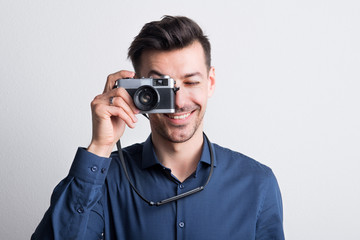 Portrait of a young man in a studio with a camera in front of his eye.
