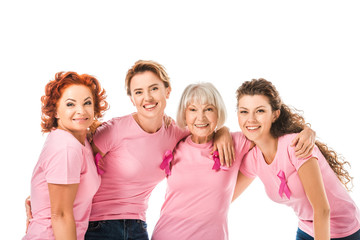 cheerful women in pink t-shirts with breast cancer awareness ribbons smiling at camera isolated on white