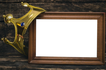 Blank photo frame border with copy space and golden crown above on wooden wall background.