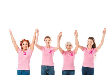 women in pink t-shirts with breast cancer awareness ribbons holding hands and smiling at camera isolated on white