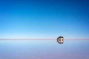 Mirror effect and reflections of a 4x4 car in Salar de Uyuni (Uyuni salt flats), Potosi, Bolivia, South America