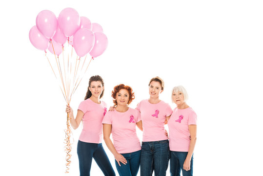 women with breast cancer awareness ribbons holding pink balloons and smiling at camera isolated on white