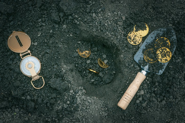 Obraz Coins, shovel and compass. Coins searching. Treasure hunting concept. In search of a lost treasure. - fototapety do salonu
