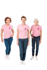 women in pink t-shirts with breast cancer awareness ribbons looking at camera isolated on white