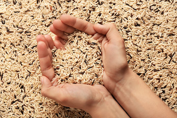 Female hands with heap of long grain rice, top view