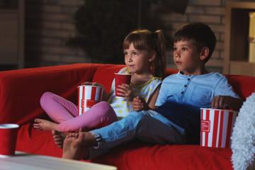 Cute children watching TV on sofa in evening