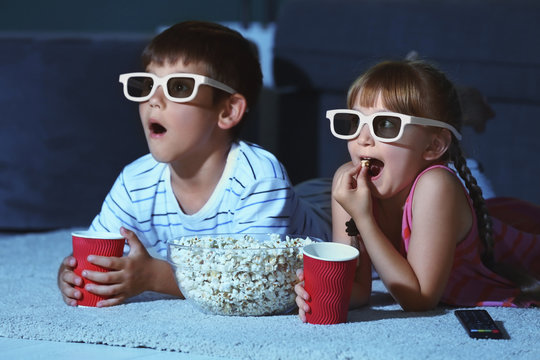 Cute children in 3d glasses watching movie on carpet in evening