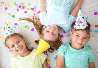 Cute little children lying on floor while celebrating Birthday at home