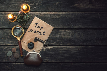 Top secret documents file, key, magnifying glass and wallet with coins on the detective spy agent table background.