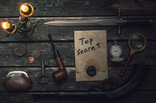 Top secret documents file, musket gun, dagger, magnifying glass, smoking pipe, pocket watch and wallet with coins on the detective spy agent.