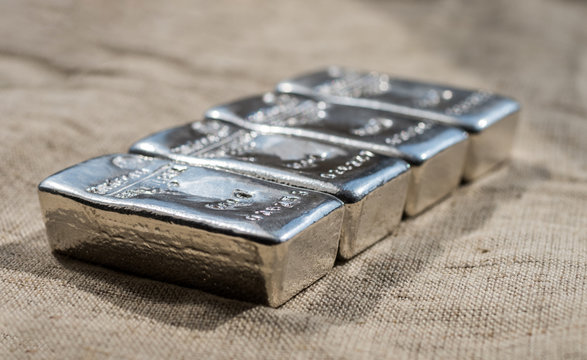 Cast silver bars against the background of the rough texture coarse cloth. Selective focus.