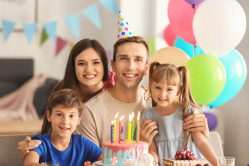 Happy family celebrating birthday at table with cake