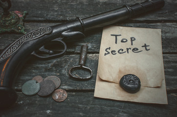 Top secret documents file, musket gun, aged key and ancient coins on the detective spy agent.