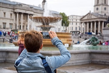 Tourist takes a photo with her smartphone in Trafalgar Square