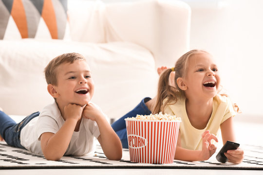 Cute children eating popcorn while watching TV at home