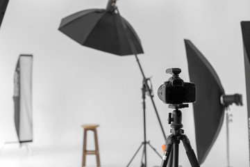 Professional camera on tripod in photo studio