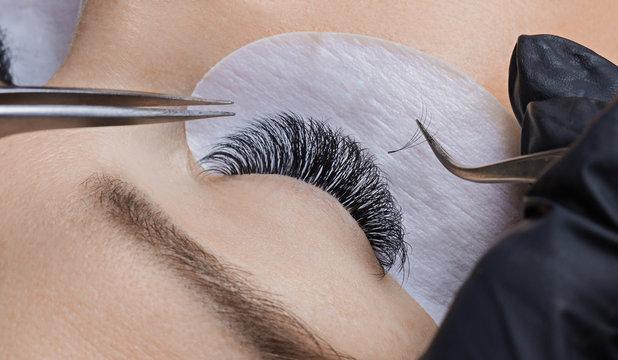 Eyelash extension procedure. Woman master making long lash