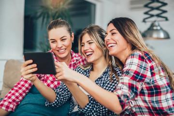 Three best friends using digital tablet together. Women sitting on sofa having fun surfing on the internet using smart digital pc tablet modern device