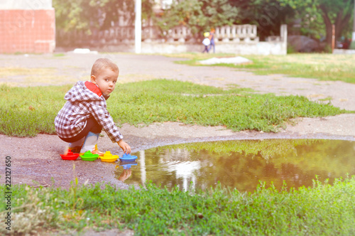 5b6396e2e A cute baby boy plays colored boats in a puddle in yellow rubber ...