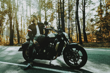 Motorcycle Biker Stops On Highway In A Forest.