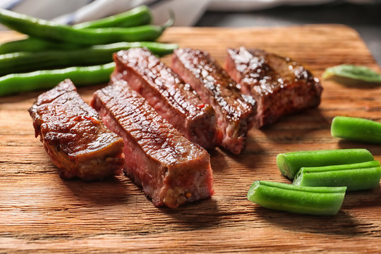 Cut grilled steak with green beans on wooden board