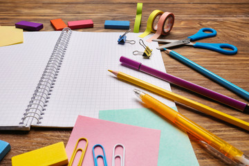 Open notebook with school stationery on wooden background