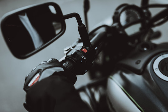 Hand In A Glove Laying On Motorcycle Steering.