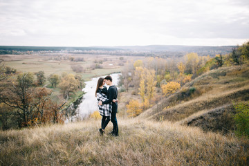 Lovers walking in the mountains. Autumn love of two happy people. Lovebirds are embracing. Beautiful place for date.