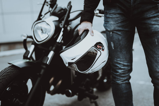Biker Holds Moto Helmet. Motorcycle On Background.