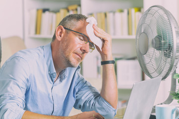 Man suffers from heat in the office or at home Wall mural
